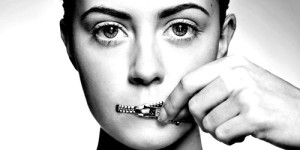 Woman zippering mouth closed